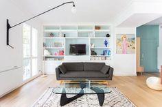 Salon cosy aux couleurs claires : canapé gris foncé, bibliothéque fonctionnelle et suspensions potence...
