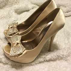 Qupid Platform Heels These peep toe heels are SO CUTE! They are a gold/beige satin color with the platform and bow at the toe. Only worn a few times. Has a slight stain on the left side of the left shoe(shown in 2nd picture) but is barely noticeable! Size 7 Qupid Shoes Heels