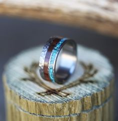 Each of our rings is a handcrafted one-of-a-kind piece, and is made to  order for you and your significant other by a passionate and skilled  artisan. This ring features a titanium lined wedding band with ironwood and  turquoise inlays. Other wood and inlay options available upon request.  Avai