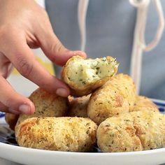 Receita com instruções em vídeo: Bolinho de aipim super crocante com um delicioso recheio de queijo coalho. Ingredientes: 600g de aipim cozido, 1 colher de sopa de manteiga, 1 pitada de sal, ½ maço de salsinha picada, 200g de queijo coalho, Farinha para empanar, Óleo para fritar