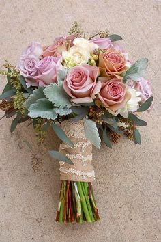 filled with 3 varieties of lavender roses, seeded eucalyptus, hypericum berries, spray roses, silver sage, and hydrangea with the handle wrapped in burlap with ivory lace accents.