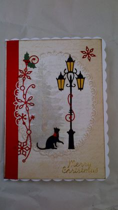 Christmas card made using Poppystamps dies.Village Lamp post, Curious Cat and Snowy Scrollwork. Cat Christmas Cards, Xmas Cards, Letter L Crafts, Handmade Christmas, Christmas Diy, Create And Craft Tv, Embossed Cards, Die Cut Cards, Marianne Design