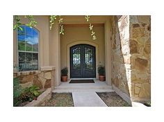 Front Door    with iron fencing. Mediterranean style home is surrounded with oak trees and forever panoramic views from front and back. 4 bedrooms plus a study with custom built-ins. Each bedroom has direct access to a bathroom. Granite counters, custom rock exterior and beautiful landscaping. Master has french door to back porch plus a huge walk-in closet. #zillow