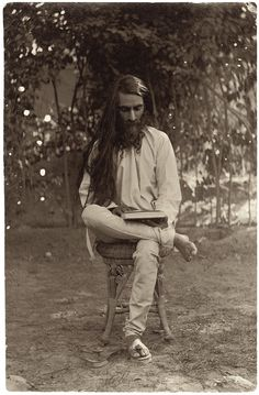 November of 1908, in the garden of his family's old home on Lawrence Road in Lahore—we see Umrao Singh Sher-gil as a young man, his curly beard still dark, his long hair unbound, sitting cross-legged in the image's gray half-tone shadows on an old-fashioned wicker stool in front of the garden wall, where the leaves on autumnal vines grow indistinct as they recede from focus. He's looking down at an unopened book on his lap.