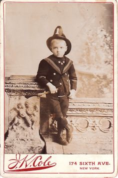 "This cabinet card features a young boy dressed up in a fireman's uniform complete with helmet. He is posing with a serious expression trying hard to play the part of an adult fireman. To make the portrait even more realistic, he is holding a fire axe. This image is another example of a cabinet card portrait that attempts to ""adultify"" children."
