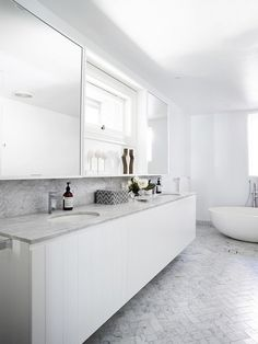 All-gray bathroom with a twin vanity, a large mirror, marble tile and a freestanding tub