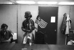 Sly Stone holds a peace flag in his backstage dressing room, circa 1960s.