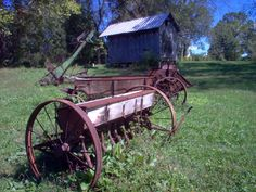 An old seeder is in the front, followed by an old manure spreader. In the background is an old elevator hay rake.