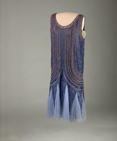First Lady Grace Goodhue Coolidge's evening gown, 1923-1929. Blue satin flapper-style evening gown trimmed with dark-blue sequins and gold glass beads. Grace Coolidge gave the dress to her White House maid, Maggie Rogers. It was likely shortened to be worn by Maggie's daughter, Lillian. American women liked Grace Coolidge's clothes, more sedate versions of the 1920s flapper style. She claimed no favorite color but did popularize red.
