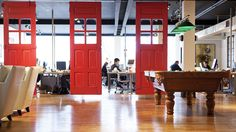 By keeping the open concept floor plan, white walls and wood floors - and incorporating a floating wall of red doors made from reclaimed materials - the office of social media firm Entrinsic nods to the heritage of the space
