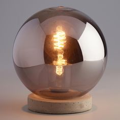 Transform your desktop with our exclusive accent lamp showcasing a vintage-style filament bulb in a smoky gray glass globe with a real concrete base. This striking art object casts a warm ambient glow.