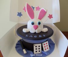 A magical rabbit in the hat themed cake created by Shandi Sansom from Sugar Kissed. Featuring an all cake rabbit and top hat with fondant cards and wand. Please visit my facebook page to see more of my work:  www.facebook.com/sugarkissedshandi