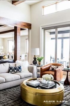 A comfy and modern living space. There are contemporary and glamorous notes with the brass cocktail table, as well as more rustic warmth via the wood beams and leather swivel chair. And the fireplace...you really have to see this incredible fireplace: https://alicelanehome.com/portfolio/glass-house/   Glass House designed by Alice Lane