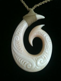 This exquisite fish hook necklace features a bone pendant with intricate hand carved details.