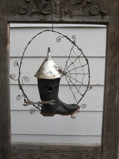 Rubber Boot bird house w/ barbed wire spiderweb frame/hanger. $ 75--, via Etsy.
