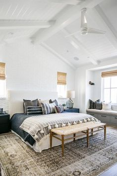 A white ceiling fan is mounted to a vaulted white plank ceiling above a rush seat bench placed on a gray overdyed rug in front of a white slipcovered bed complemented with dark blue bedding accented with a white and gray striped tassel throw blanket topped with layered gray pillows.