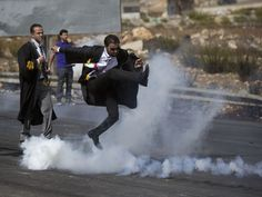 A lawyer wearing his official robes kicks a tear gas canister back toward Israeli soldiers during a demonstration by Palestinian lawyers called for by the Palestinian Bar Association in solidarity with protesters at the Al-Aqsa Mosque compound in Jerusalem's Old City near the West Bank city of Ramallah.  Majdi Mohammed, AP