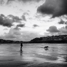 Dog walker on beach Cornwall - Black and white