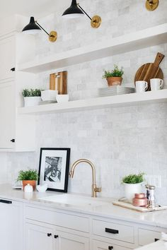 White floating shelves are mounted to gray marble subway tiles beneath Aerin Cha. - White floating shelves are mounted to gray marble subway tiles beneath Aerin Charlton Sconces posit - Shelves Over Kitchen Sink, Floating Shelves Kitchen, Light Above Kitchen Sink, Kitchen Tiles, Kitchen Lighting, White Shaker Kitchen, White Shaker Cabinets, Inset Cabinets, Marble Subway Tiles