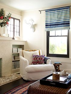 Simple white upholstery ensures the expensive living room chairs will be in style for years to come. Outfitting the neutral living room with colorful throws, accent pillows, and window shades adds needed color to the space that can be easily switched out as trends change over the years.
