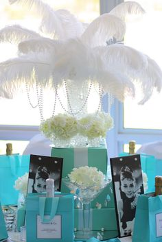 Breakfast at Tiffany's Table: Wrapping paper from Sophia's Favors on boxes with the insides cut out to hold an Eiffel tower vase with peacock feathers. Faux diamond napkins rings from Hobby Lobby. Turqouise napkins, runner and chair sashes from TableLinen Factory. Martini glasses filled with diamonds and pearls and hydrangeas. Audrey pics from WALMART. Champagne with either cat or dog masks in blue bags as gifts. bags had some great quotes on them as well. Hydrangeas, silver charges. Tiffany Blue Party, Tiffany Birthday Party, Tiffany Theme, Tiffany Wedding, Tiffany And Co, Birthday Parties, Gold Wedding, Surprise Birthday, Purple Wedding