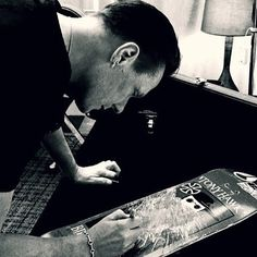 """Larry Mullen Signing The Skateboard with Lyrics from """"Where The Streets Have No Name"""""""