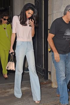 Amal Clooney wearing Stella McCartney Sunfaded Flared Jeans and Dior Tribal Earrings
