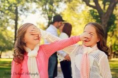 Twin girls hide eyes from mom and dad kissing, natural lighting, outdoor, children photography by Natalie Eberhard in Nevada, Missouri