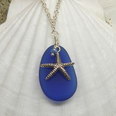 """This is our cultured sea glass necklace featuring a textured starfish and hand wrapped blue crystal dangling on top of a piece of royal blue man-made sea glass on a 20"""" alloy chain. The sea glass is 1"""