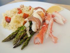 Asparagus and King Crab wrapped in Prociutto topped with a lemon and roasted garlic aioli. This is served with more king crab and and a roasted red pepper couscous.