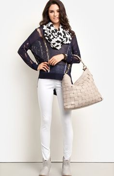 A sheer navy sweater looks chic yet cool with white skinnies, a large gray woven tote and matching perforated ankle boots.