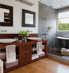 Ducha y madera compartiendo espacio. Para aprovechar mejor los metros disponibles, la ducha y la bañera de hierro fundido comparten espacio, y la grifería del lavamanos se ha empotrado en la pared. El mueble bajolavabo de roble es diseño de SC 21 Interiorismo. El lavamanos, la grifería, la bañera y la ducha, adquiridos en Trentino.