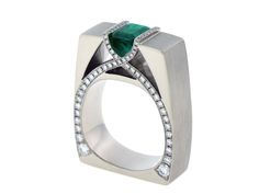 One custom designed and crafted 14k palladium white gold raised channel set ring for clients synthetic emerald. Ring is pave set along the top and one side face with round brilliant diamonds.