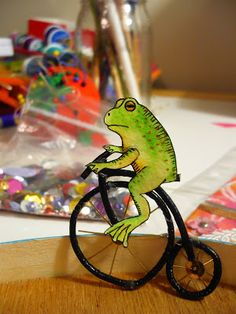 """Tiny frog on tiny old-timey bicycle"" (by Kira Nichols)"