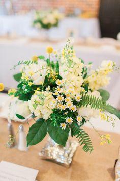 farm table centerpiece arrangement of pale yellow stock, cream roses, white roses, billy balls, button chamomile, white lisianthus, bupleurum, lemon leaf & fern on a mercury glass pedestal.