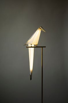 Bird lamp. A lamp designed in a bird's shape seemingly perched n a branch and projecting light from its body.