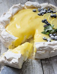 A delicious, light and fresh dessert with a meringue base and a light lemon curd topping, garnished with fresh lemon slices, blueberries, mint leaves and powdered sugar. Lemon Curd Pavlova - Seasons and Suppers Lemon Desserts, Köstliche Desserts, Lemon Recipes, Sweet Recipes, Delicious Desserts, Yummy Food, Lemon Curd Dessert, Lemon Curd Cake, Plated Desserts