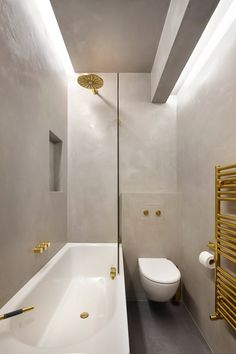 Glenshaw Mansions by Rise Design Studio Light grey Tadelakt – a waterproof lime plaster used on both the interior and exteriors of buildings – was used for the bathroom walls, and is punctured with brass fittings.