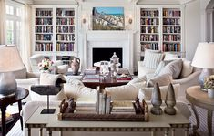 """The bookshelves in the living room """"are carefully calculated to fit within the coffered ceiling,"""" Hampton notes. The Lifeguard, by Thomas L. Tribby, hangs above the mantel. Ralph Lauren hurricane lamps. Duck decoy, Sentimento Antiques. Club chair fabric, Fabricut. Light blue sofa pillow fabric, Cowtan & Tout. Drapery fabric, Rogers & Goffigon."""