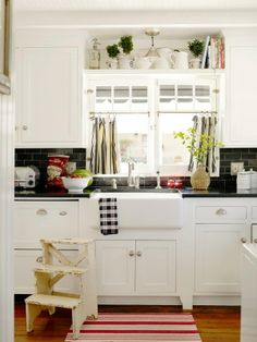 white kitchen with touches of black and red - love the shelf over the window