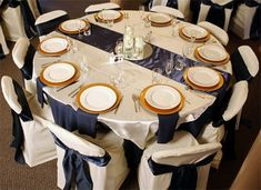 White, Navy Blue and Gold : Navy Blue 120inch round polyester tablecloth with a navy blue satin runner and navy blue 17inch napkins. White 60 inch square satin overlay and white square banquet chair covers. Gold chargers give it that extra elegance and color