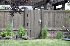 Dark stained wooden fence with lower brick base looks great together