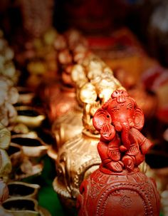 Lord Ganesh idol made of clay and painted red floowed by golden colored Ganesha statues.