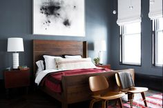 A dark moody bedroom with charcoal walls and red accents.