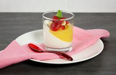 A photo of Greek Yogurt Panna Cotta layered with Citrus Gelee and topped with fresh Berry Compote served in a dessert glass.