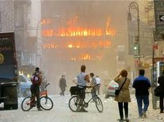 Witnesses watch flames spew from one of the several buildings -- in addition to the Twin Towers -- damaged or destroyed in lower Manhattan. | September 11, 2001