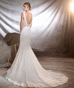 Pronovias Oreste bridal gown. Suggestive empire line mermaid wedding dress with a bateau neckline. A perfect combination of crepe, tulle and lace floral motifs. There's a glimpse of a suggestive sweet