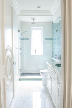 Bathroom designed by Enviable Designs - A central window opening brightens the interior bath with accent turquoise subway tiles and multiple blue tone mosaic for shower floors.