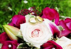 Golden wedding rings on a bridal bouquet with pink roses -