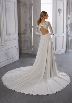 The A-line wedding dress has a lace bodice with a v-neckline, long sleeves, and heyhole back with a chiffon skirt. Long Sleeve Bridal Dresses, Bridal Wedding Dresses, Mori Lee, Chiffon Skirt, Lace Bodice, Neckline, Formal Dresses, Skirts, Collection